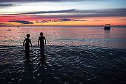 Children are silhouetted at sunset on a Cape Cod beach.