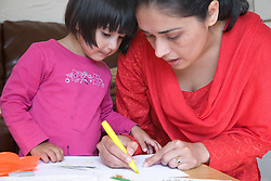 Mother showing her daughter how to draw,