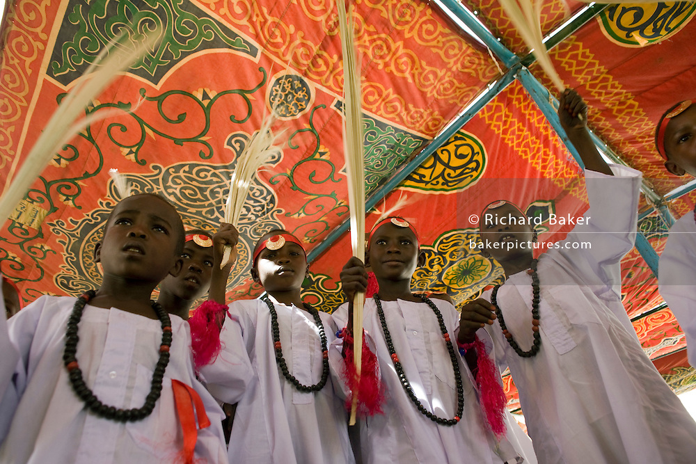 Young boys between the ages of 8 and 13 gather under the shade of a brightly-coloured canopy in the compound of the Govenor of the war-torn region of north Darfur, Sudan. Dressed in white gowns and wearing red bandanas, they will soon celebrate a Sudanese rite of passage, the male circumcision. When they have recited the entire Qur'an [Koran] once through will they generally endure this traditional practice