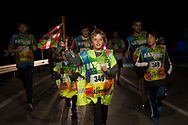 """People run on the 20th Korrika. Cintruenigo (Basque Country). April 1, 2017. The """"Korrika"""" is a relay course, with a wooden baton that passes from hand to hand without interruption, organised every two years in a bid to promote the basque language. The Korrika runs over 11 days and 10 nights, crossing many Basque villages and cities. This year was the 20th edition and run more than 2500 Kilometres. Some people consider it an honour to carry the baton with the symbol of the Basques, """"buying"""" kilometres to support Basque language teaching. (Gari Garaialde / Bostok Photo)"""