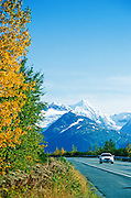 Alaska. A car driving down the scenic Seward Highway, Chugach Mts in background.