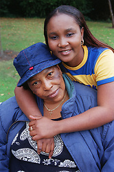 Teenage girl standing in park smiling with arms around woman,