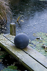 Frozen pond with decorative ball on wooden jetty