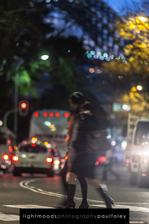 People crossing a street after work, with Sydney Harbour Bridge in background, Australia. Motion blur.