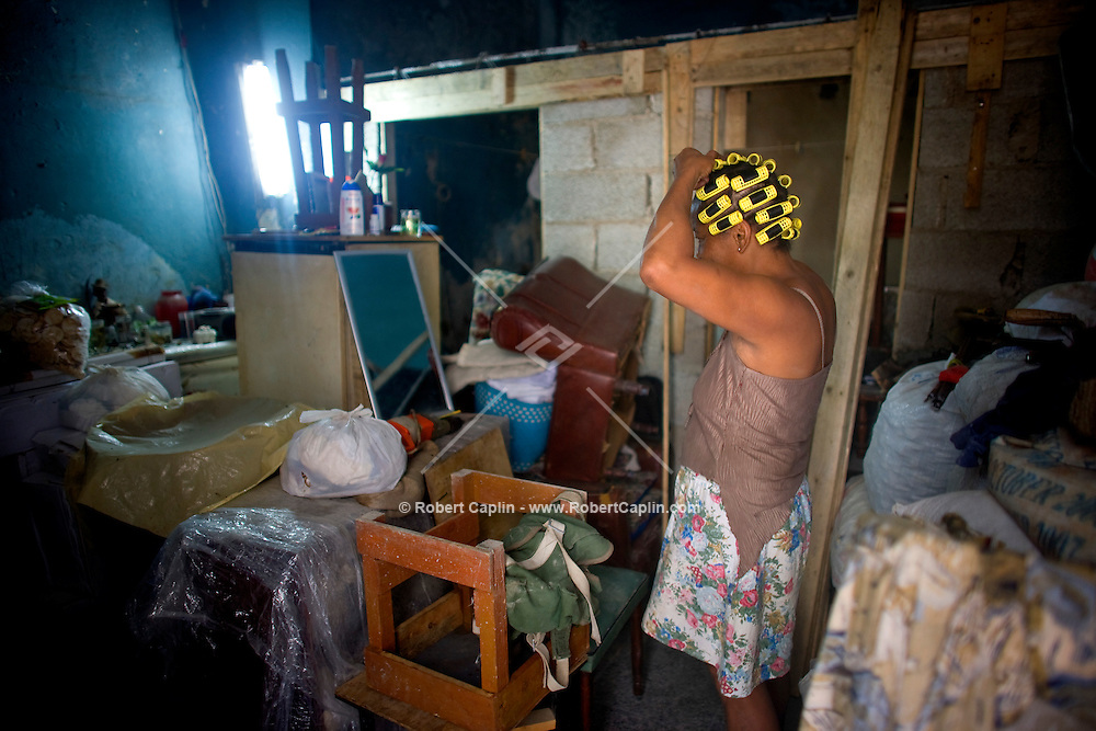 old cuban woman doing her hair in cluttered room