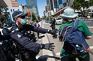 A officer orders a protester to stand clear during an Extinction Rebellion protest in Melbourne.  A small group of climate protesters marched from Flagstaff Gardens to The Queen Victoria Market and ending with two individuals gluing themselves together, and then glued themselves to Victoria Avenue outside of the Market. This comes as 5 new COVID-19 cases were uncovered in Melbourne's revamped Hotel Quarantine, breaking almost 40 days of virus free days. (Photo by Dave Hewison/Speed Media)