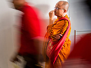 """23 FEBRUARY 2014 - NAKHON RATCHASIMA (KORAT), NAKHON RATCHASIMA, THAILAND: A Buddhist monk listens to Red Shirt speakers while people walk in and out of the Red Shirt meeting in Korat. The United front of Democracy against Dictator (UDD or Red Shirts), which supports the elected government of Yingluck Shinawatra, staged the """"UDD's Sounding of the Battle Drums"""" rally in Nakhon Ratchasima (Korat) to counter the anti-government protests that have gripped Bangkok since November. Around 4,000 of UDD's regional and provincial coordinators along with the organization's core members met at Liptapunlop Hall inside His Majesty the King's 80th Birthday Anniversary Sports Complex in Korat to discuss the organization's objectives and tactics against anti-government protestors, which the UDD says """"seek to destroy the country's democracy."""" The UDD leadersa announced that they will march to Bangkok and demonstrate against anti-government protests led by Suthep Thaugsuban.   PHOTO BY JACK KURTZ"""