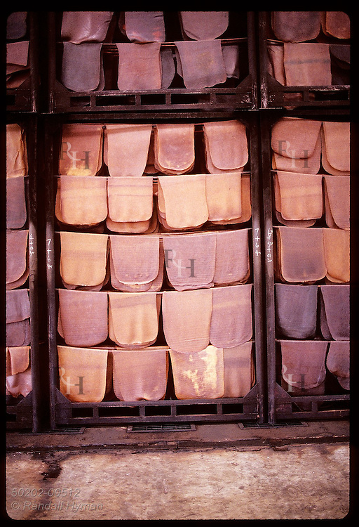 Rubber mats hang on bamboo poles in smokeroom to undergo final drying before export; (v) Krabi. Thailand