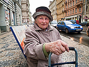 "A pensioner is resting on a bench at ""Ujezd"" waiting for a tramway."
