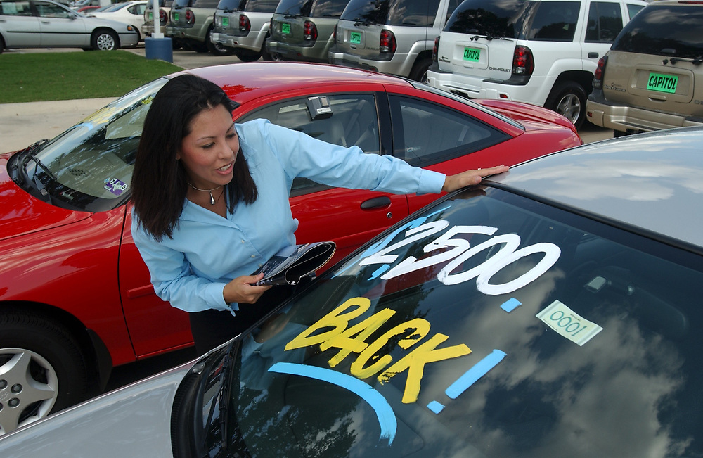 """Austin, Texas August 20, 2003: Hispanic woman (28) ) shops for a new car at a Chevrolet GM dealership on the """"motor mile"""" of south Austin. With the economy in the doldrums, salespeople are finding it tough to entice buyers into new vehicles this summer. MODEL RELEASE SP-40 Hispanic female.  ©Bob Daemmrich"""