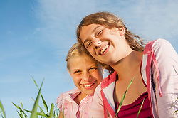 Two girls (10-11) (12-13) in meadow, smiling, portrait, close-up