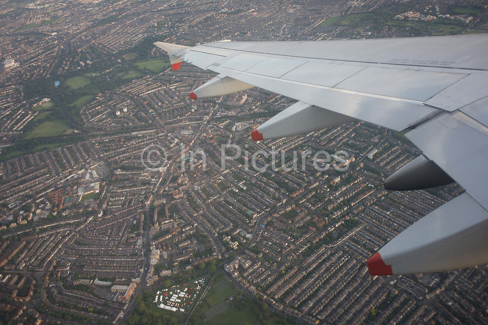 A airliner window seat view of west London as the aircraft comes in to land at London's Heathrow airport. The campaign for a 3rd runway at Heathrow is being met by fierce opposition due to the nature of constantly low-flying planes over residential areas. From the chapter entitled 'Up in the Air' and from the book 'Risk Wise: Nine Everyday Adventures' by Polly Morland (Allianz, The School of Life, Profile Books, 2015).