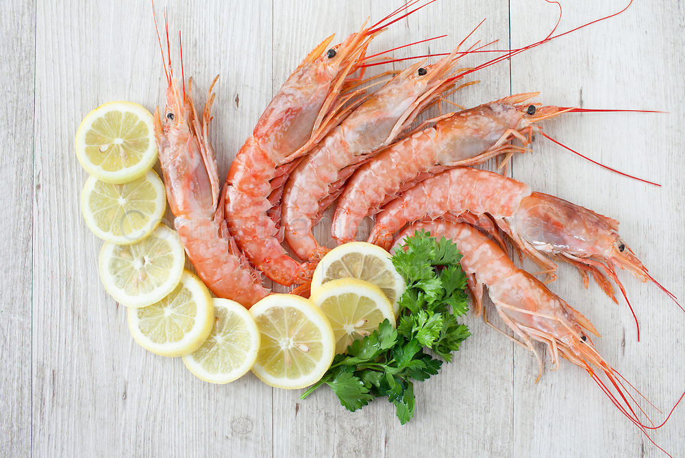 Fresh mediterranean prawns with lemon slices and parsley, flat lay.