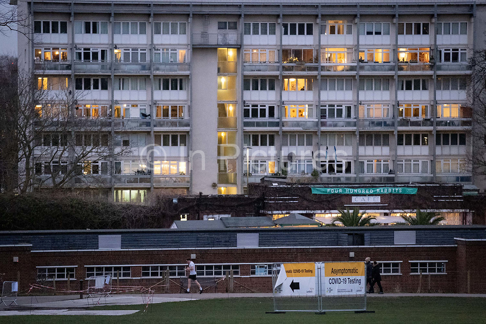 South Londoners pass beneath residential flats and a sign pointing towards an asymptomatic COVID-19 testing centre has been set-up in Brockwell Park in Lambeth and during the third pandemic lockdown, on 9th January 2021, in London, England. Government ministers are to discuss proposals to pay anyone in England who tests positive for Covid-19 £500 to self-isolate. Many workers are currently strugling financially because low paid workers cannot afford to self-isolate.