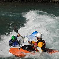 Kayakers wave surf on Kananaskis River in the Canadian Rockies near Calgary, Alberta.