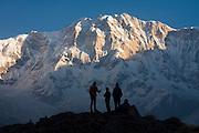 Trekkers enjoy the sunrise views of the dramatic South Face of Annapurna I (8091m) from Annapurna Base Camp, Annapurna Sanctuary, Himalaya Mountains, Nepal.