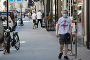 Man wearing a face mask and an England t-shirt as the Coronavirus lockdown measures are set to ease further, the west end starts to fill with people as they return to the shopping district on Bond Street and the quiet city starts coming to an end on 22nd June 2020 in London, England, United Kingdom. As of today the government has relaxed its lockdown rules, and is allowing some non-essential shops to open with individual shops setting up social distancing queueing systems.
