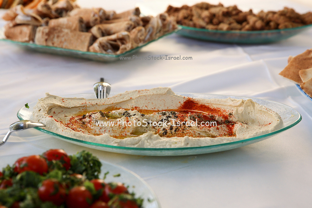 A buffet table set with salads and appetizers - main focus on a dish of hummus