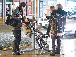 © Licensed to London News Pictures . 01/01/2015 . Manchester , UK . A woman attempts to ride a bicycle that is padlocked to a lamppost . Revellers usher in the New Year on a night out in Manchester City Centre .  Photo credit : Joel Goodman/LNP