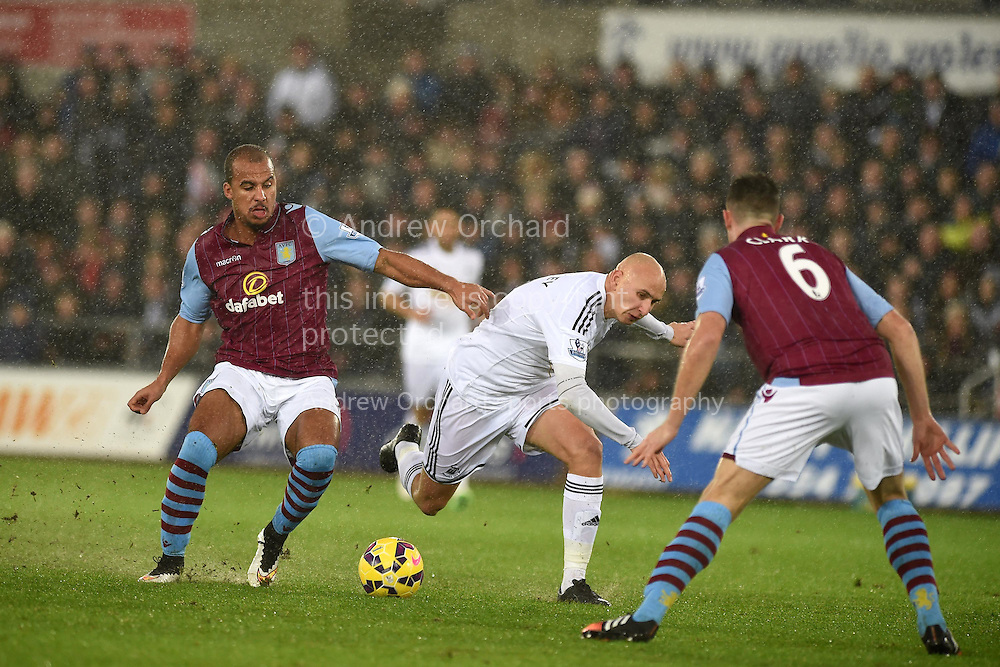 Jonjo Shelvey of Swansea © is tackled by Aston Villa's Gabriel Agbonlahor.  Barclays Premier league match, Swansea city v Aston Villa at the Liberty stadium in Swansea, South Wales on Boxing Day, Friday 26th December 2014<br /> pic by Andrew Orchard, Andrew Orchard sports photography.