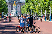 Geting others to take photos despite the contamination risk - Enjoying cycling on The Mall as the sun comes out again. The 'lockdown' continues for the Coronavirus (Covid 19) outbreak in London.