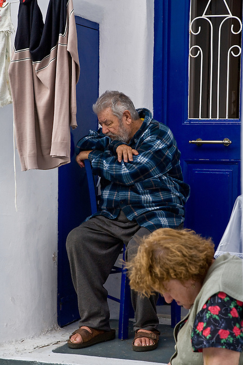 Elderly couple takes an afternoon nap on the Greek Island of Mykonos in their doorway with laundry drying.