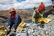 Las mujeres y niñas trabajan en el exterior de la mina buscando oro entre los fragmentos de roca que son arrojados del interior del socavón, en La Rinconada, Perú, 2012. Debido a las creencias, las mujeres tienen prohibido entrar a los socavones para evitar que el mineral se esconda y no pueda ser hallado.