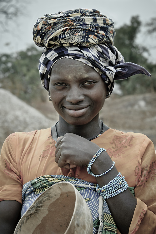 Stock photograph of a Guinean woman posing with a calabash for of gold nuggets.
