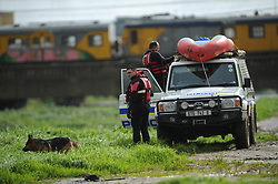 South Africa - Cape Town - 10 July 2020 - Rescue workers next to the Blackriver.  An eight-year-old girl and a man in his 30s are feared drowned after stormwaters swept them away in an Athlone canal on Thursday afternoon. Abieda Steenkamp and two of her friends were playing on the banks of the canal in Klipfontein Road, close to Calendula in Vygieskraal, when the banks apparently burst as a result of heavy rainfall, and the children fell into the fast-flowing river. The little girl drifted and disappeared under the water while her two friends managed to get out. Witnesses say the unidentified man jumped into the water to help the girl, but he too got swept away by the strong current.<br /> Speaking to the Daily Voice at the scene, Michael said the children were playing next to the canal when they all slipped and fell in. The search was suspended at 13:00. The divers stopped their search opposite the intersection of Black river Parkway and Berkley Road due the thick undergrowth in the river. Picture: Henk Kruger/African News Agency(ANA)