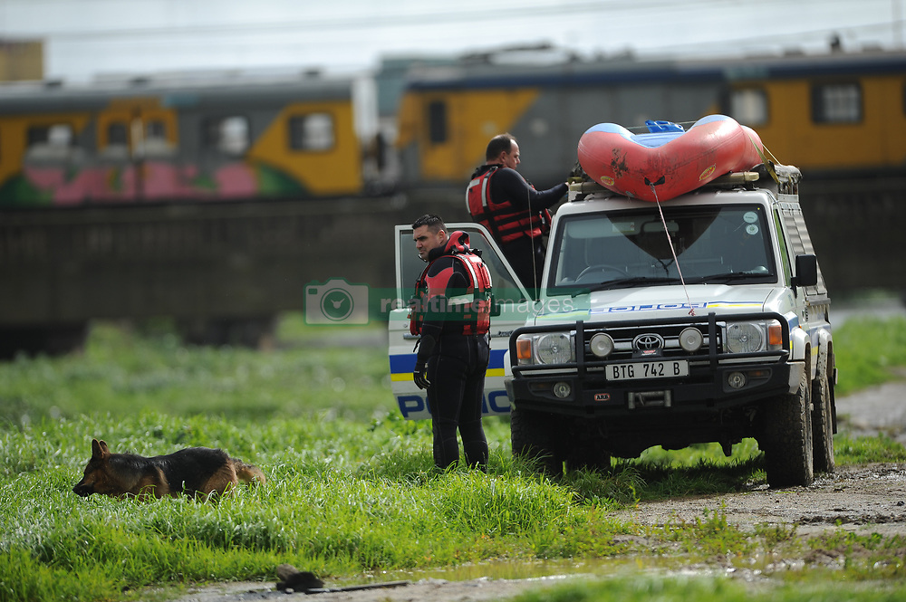 South Africa - Cape Town - 10 July 2020 - Rescue workers next to the Blackriver.  An eight-year-old girl and a man in his 30s are feared drowned after stormwaters swept them away in an Athlone canal on Thursday afternoon. Abieda Steenkamp and two of her friends were playing on the banks of the canal in Klipfontein Road, close to Calendula in Vygieskraal, when the banks apparently burst as a result of heavy rainfall, and the children fell into the fast-flowing river. The little girl drifted and disappeared under the water while her two friends managed to get out. Witnesses say the unidentified man jumped into the water to help the girl, but he too got swept away by the strong current.<br /> Speaking to theDaily Voiceat the scene, Michael said the children were playing next to the canal when they all slipped and fell in. The search was suspended at 13:00. The divers stopped their search opposite the intersection of Black river Parkway and Berkley Road due the thick undergrowth in the river. Picture: Henk Kruger/African News Agency(ANA)