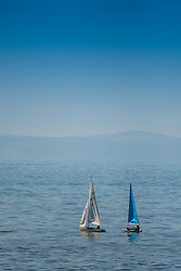© Licensed to London News Pictures. 15/03/2017. Aberystwyth, Wales, UK. Two small sailing dinghies out on the flat calm water of Cardigan Bay on a day of clear blue skies and brilliant unbroken warm springtime sunshine in Aberystwyth Wales .Photo credit: Keith Morris/LNP