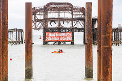 © Licensed to London News Pictures. 29/08/2020. Brighton, UK. Members of the Extinction Rebellion protest group hung a banner on the Brighton's West pier remains aead of their weekend of protests. Photo credit: Hugo Michiels/LNP