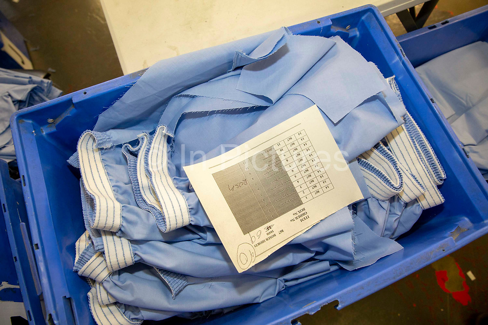 Blue uniform boxer shorts material sits in a blue box in the workshop in the Industries Department in Her Majesty's Prison Pentonville, London, United Kingdom.  Prisoners are encouraged to work or take courses to learn new skills to help rehabilitation and reduce re-offending rates on their release.