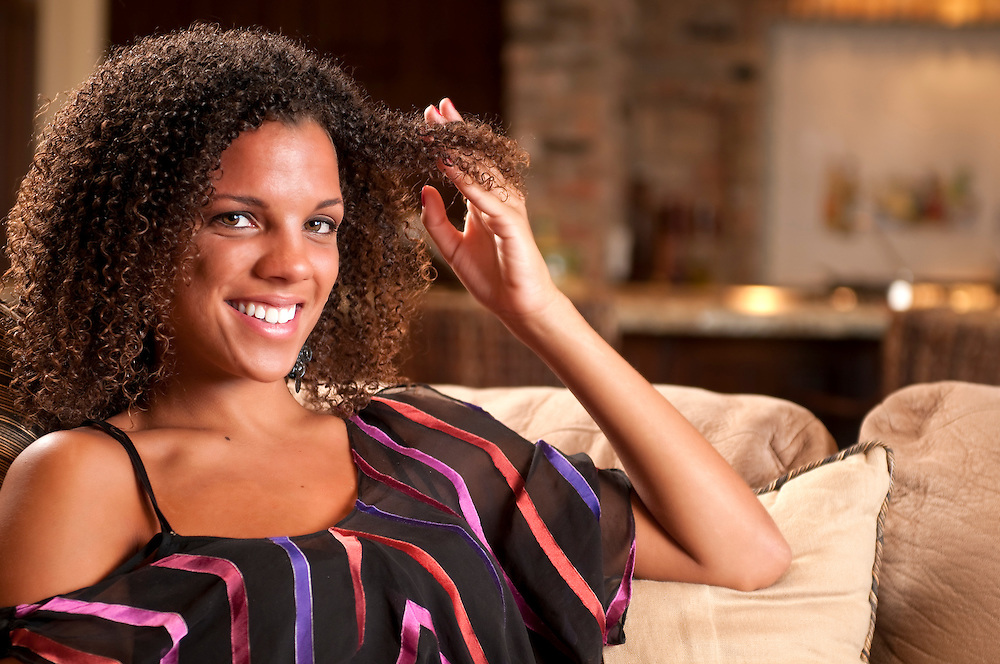 Young woman playing with curly hair in the family room.