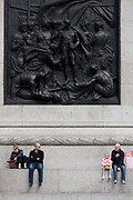 Tourists sit beneath The Battle of Cape St Vincent by Musgrave Watson and William F. Woodington, the relief on the west face of the plinth on Nelson's Column in Trafalgar Square. Two men in almost identical clothing and bald heads look across to each other while sitting under the detail of one of Britain's naval victories against Napoleon's French in 1797 led by one its national heroes, Admiral Horatio Nelson whose memorial is the column in the heart of central London.
