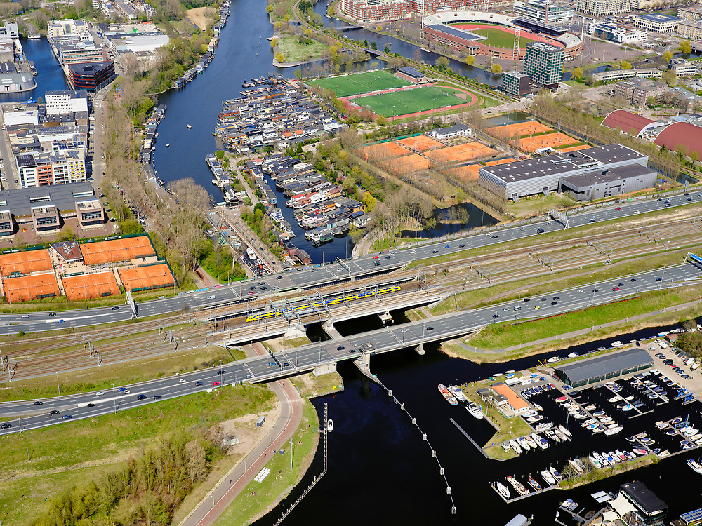 Nederland, Noord-Holland, Amsterdam; 17-04-2021; Zuidas, begin ring A10, A10 Zuid. Zicht op de Schinkelbruggen, spoorlijn met intercity richting Schiphol. Aan gene zijde van de A10 het IJsbaanpad met woonschepen en de Nieuwe Meersluis. Onder in beeld jachthavens in de Nieuwe Meer. <br /> Zuidas, start of ring A10, A10 South. View of the Schinkel bridges, railway with intercity to Schiphol. On the other side of the A10 the IJsbaanpad with houseboats and the Nieuwe Meersluis. At the bottom of the picture marinas in the Nieuwe Meer.<br /> <br /> luchtfoto (toeslag op standaard tarieven);<br /> aerial photo (additional fee required)<br /> copyright © 2021 foto/photo Siebe Swart