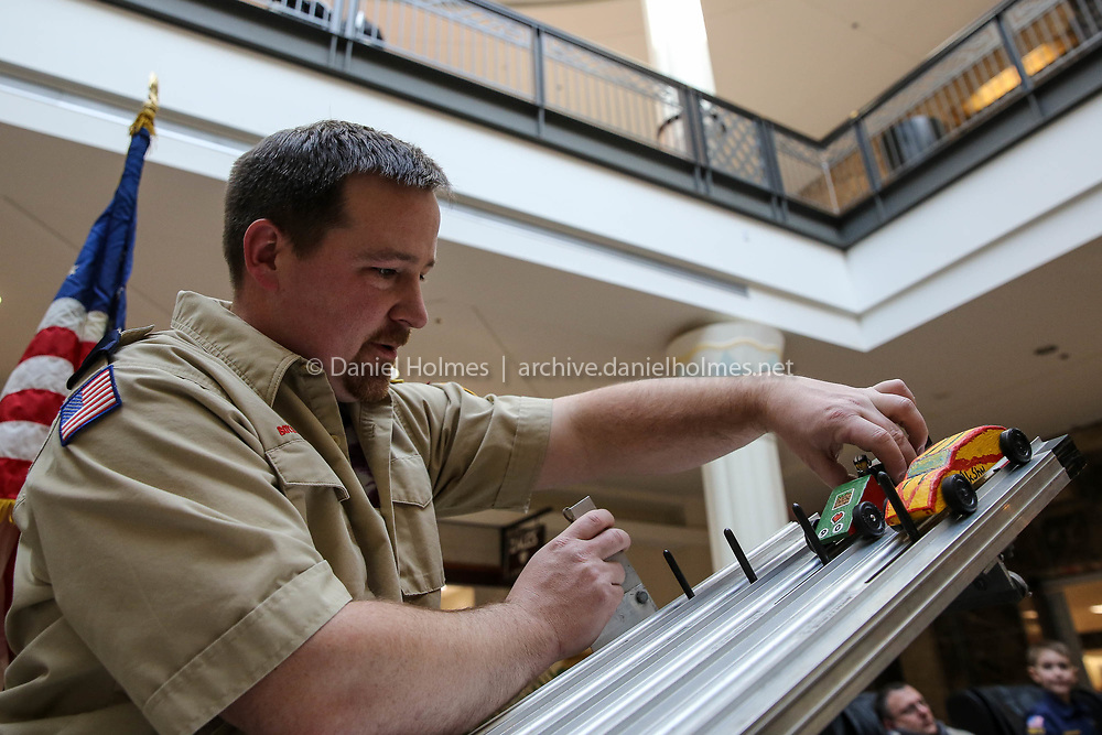(1/27/18, MARLBOROUGH, MA) Cub-master Mark Cullen places derby cars on the track during the Pinewood Derby for the Northborough Cub Scouts at the Solomon Pond Mall in Marlborough on Saturday. [Daily News and Wicked Local Photo/Dan Holmes]