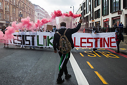 A man holding a smoke grenade walks in front of a Resist Like Palestine banner during a Free Palestine SOS Colombia march in solidarity with the Palestinian and Colombian peoples from the Colombian embassy to the Israeli embassy on 15th May 2021 in London, United Kingdom. Speakers at a rally before the march, which took place on Nakba Day, highlighted human rights abuses being directed against Palestinians in Israel and the Occupied Territories, in particular attempts at forced displacements in Sheikh Jarrah in East Jerusalem, and also in Colombia, where peaceful demonstrators and human rights defenders have been killed and subjected to repression, detention and torture.