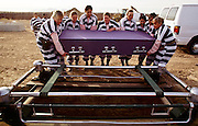 """01 NOVEMBER 1999  - PHOENIX, ARIZONA, USA: Members of the women chain gang in Maricopa County, Phoenix, AZ, bury a homeless person in the county's """"Potter's Field"""" or cemetery for the indigent. Maricopa county sheriff Joe Arpaio claims to have the only women's chain gang in the United States. He has been criticized for the chain gang but claims to be an """"equal opportunity incarcerator."""" He has said that if puts men on a chain gang he will also put women on a chain gang. The women are prisoners in the county jail and volunteer for duty on the chain gang because it gets them out of the jail for six hours a day. The chain gang also buries the county's homeless and indigents.   © Jack Kurtz  WOMEN   PRISON   CIVIL RIGHTS  SOCIAL ISSUES    POVERTY"""
