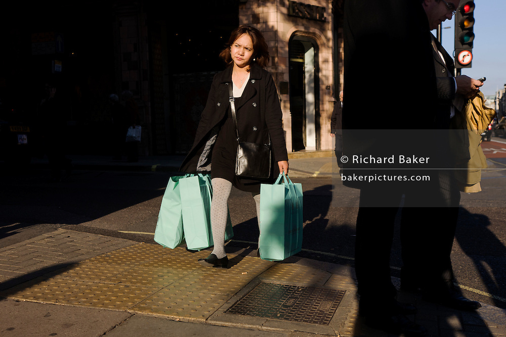 Woman shopper carries her bags along Piccadilly in late afternoon sunshine.