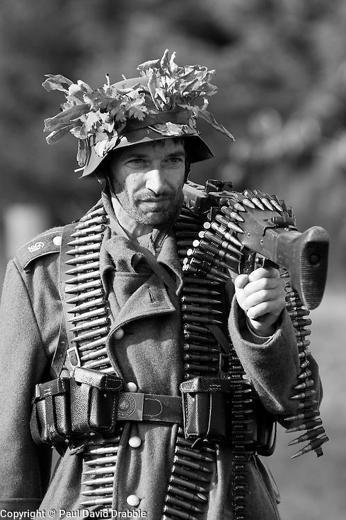German Machine Gunner from the Grossdeutschland Division carrying an MG42 machine gun and ammunition belts, <br /> portrayed by a world war two reenactor.