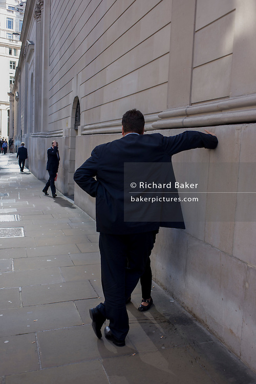 A businessman talks to an unseen woman on Lothbury Street in the City of London, the capital's financial district and oldest quarter.