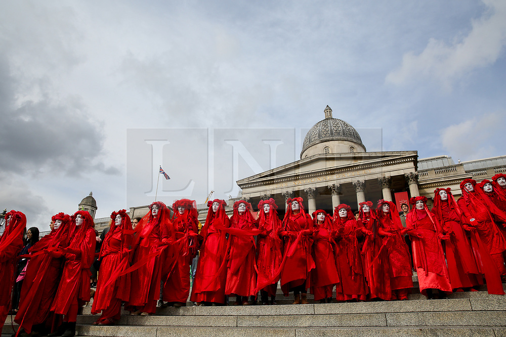 © Licensed to London News Pictures. 09/10/2019. London, UK. The Red Brigade of The Invisible Circus perform on the steps of Trafalgar Square on day three of the two weeks protest. The activists are calling for the government to act on climate change. Photo credit: Dinendra Haria/LNP