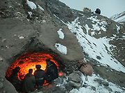Kyrgyz men seek shelter in a shepherd's cave during the icy five-day trek down from their mountainous homeland to the nearest trading village in Afghanistan. They will barter livestock, wool, and dairy products for everything from tea to television sets.<br /> <br /> In Zan Kuk. <br /> Trekking back down from the Little Pamir, with yak caravan, over the frozen Wakhan river.