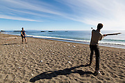 Henry (pitcher) and Zach Podell-Eberhardt (batter) play baseball with driftwood on Tsusiat Beach, West Coast Trail, British Columbia, Canada.