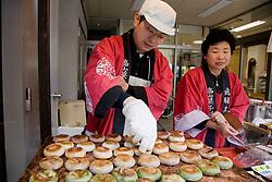 Asia, Japan, Gifu prefecture, Takayama (also known as Hida-Takayama), man cooking traditional sweet desserts at food stall on street