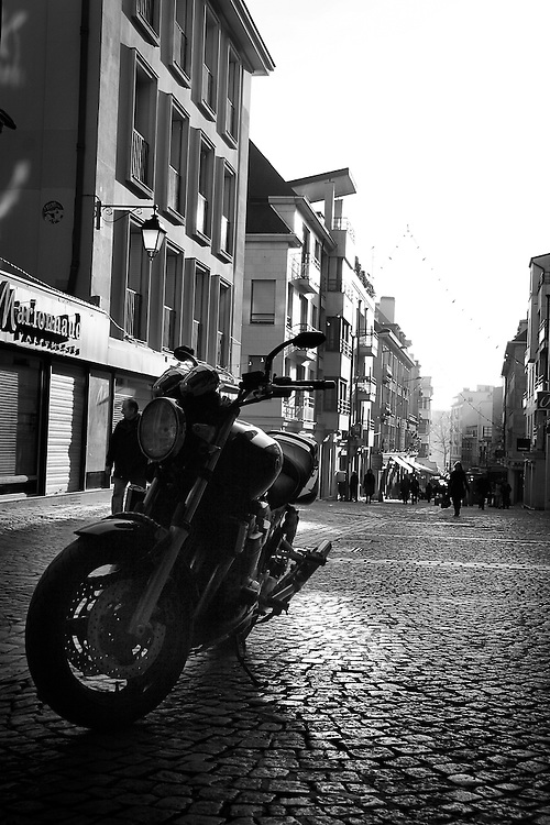 A lone motorcycle is parked on a walking avenue in Rouen, France.