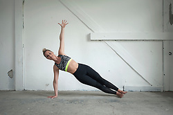 Mid adult woman practicing side plank pose in yoga studio, Munich, Bavaria, Germany