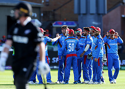 Afghanistan's Hamid Hassan celebrates catching New Zealand's Colin Munro with team mates during the ICC Cricket World Cup group stage match at the County Ground Taunton.