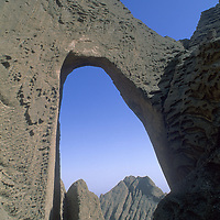 CHINA, Xinjiang Province.  Tiny climbers (MR) stand atop huge Shipton's Arch in Kara Tagh Mountains near Kashgar & Taklimakan Desert.